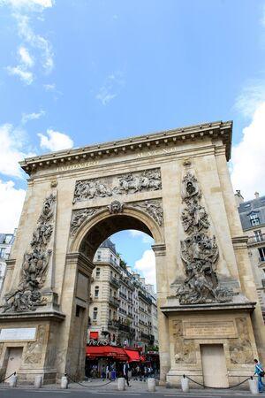 incidental people: PARIS, FRANCE - AUG 18, 2014: Porte Saint-Denis triumphal arch with the entablature bronze inscription LUDOVICO MAGNO, To Louis the Great
