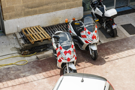 a white police motorcycle: MARSEILLE, FRANCE - JUL 19, 2014: Three tunnel security motorcycles parked outside the building near a tunnel in Marseille, France
