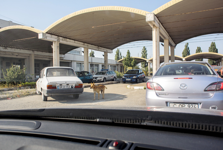 customs official: ROMANIA - AUG 16: Romanian Bulgarian border customs control with typical Soviet architecture and homeless dog
