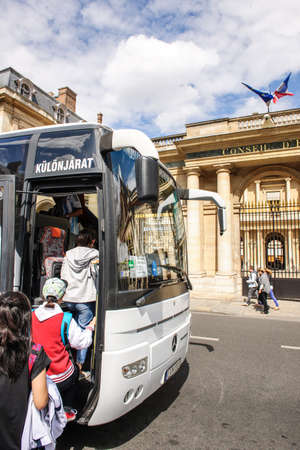 coach bus: PARIS, FRANCE - AUG 18, 2014: Hungarian tourists entering white tourist coach bus after visiting Louvre Museum and the building of Conseil dEtat in Paris, France Editorial