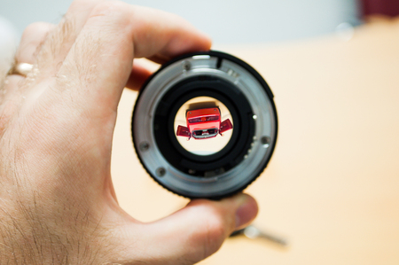 automobile dealership: Anticipation of a new dream car - man holding camera lens with the new car inside Stock Photo