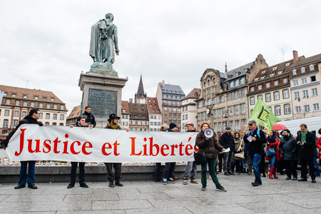protesting: PARIS, FRANCE - JAN 30, 2016: Protesters gathered at Kleber Square Place Kleber during a demonstration, protesting governments plan of the extension of the state of emergency for another three months - Justice and Freedom placard