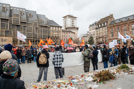 precarious: PARIS, FRANCE - JAN 30, 2016: Protesters gathered at Kleber Square Place Kleber during a demonstration, protesting governments plan of the extension of the state of emergency for another three months - people holding placard