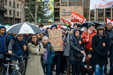 precarious: PARIS, FRANCE - JAN 30, 2016: Protesters gathered at Kleber Square Place Kleber during a demonstration, protesting governments plan of the extension of the state of emergency for another three months - people under rain at protest Editorial