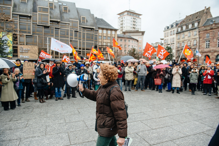 addressing: PARIS, FRANCE - JAN 30, 2016: Protesters gathered at Kleber Square Place Kleber during a demonstration, protesting governments plan of the extension of the state of emergency for another three months - old woman addressing to crowd
