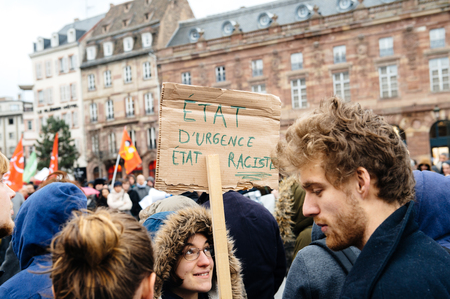 anti racist: PARIS, FRANCE - JAN 30, 2016: Protesters gathered at Kleber Square Place Kleber during a demonstration, protesting governments plan of the extension of the state of emergency for another three months - hlding placard - Emergency State - Racist State, Editorial