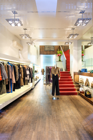 Interior of a boutique store with fashionable luxury women dresses. Clothed female dummy with clothes on it - seen from the street Editorial