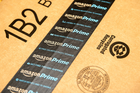 PARIS, FRANCE - JAN 28, 2016: Amazon Prime logotype printed on cardboard box security scotch tape. Amazon Prime is a service from Amazon which delivers parcels in 1 day, streams unlimited music and video gives access to unlimited Books on Kindle store. Am Editoriali