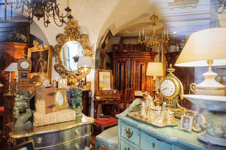 VIENNA, AUSTRIA - JULY 4, 2011: Antiquities shop window shopping seen from the street - Kohlmarkt street in Vienna. The vintage store sells old clocks, old mirrors, old table sets, old furniture, vintage objects, vintage lamps, vintage books and other hob Editorial