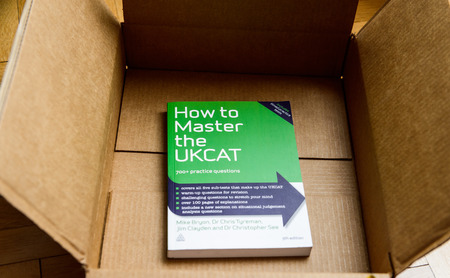 situational: PARIS, FRANCE - JAN 28, 2016: Cardboard box containing the book How to Master the UKCAT for admission to the medicine school