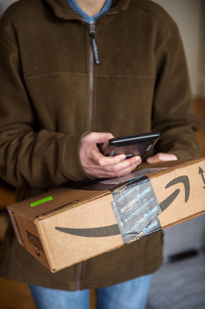 prime adult: PARIS, FRANCE - JAN 27, 2016: UPS United Parcel Service young female postal delivery courier in front of door scanning the  ontime delivering package from Amazon Prime