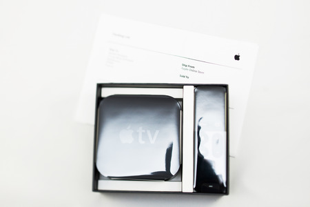 motion sensor: PARIS, FRANCE - NOV 10, 2015: New Apple TV media streaming  player microconsole by Apple Computers - unboxing and Apple Store invoice. It has new touch remote swipe-to-select with integrated Siri and motion sensor