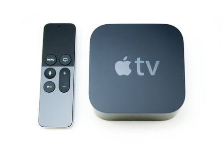 MANZANA: PARIS, FRANCIA - 10 de noviembre, 2015: Nuevo Apple TV medios reproductor de streaming MicroConsole por Apple Computers próximos al nuevo toque de golpe-a-seleccione remoto con sensor integrado Siri y el movimiento en blanco