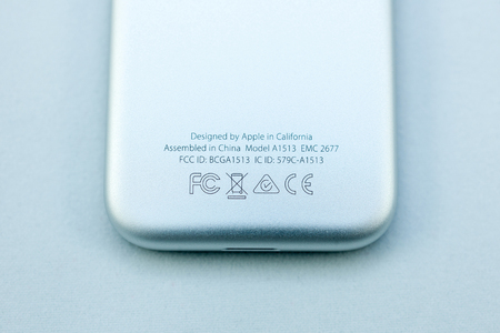 motion sensor: PARIS, FRANCE - NOV 10, 2015: Extreme colseup of the bottom rear of the Apple TV media streaming  player microconsole by Apple Computers futuristic touch remote swipe-to-select with integrated Siri and motion sensor