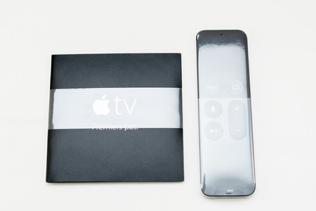 instruction manual: PARIS, FRANCE - NOV 10, 2015: New Apple TV touch remote in plastic film with swipe-to-select & integrated Siri and motion sensor next to instruction manual Editorial