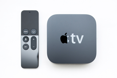 tv remote: PARIS, FRANCE - NOV 10, 2015: Focus on the remote control of the New Apple TV media streaming  player microconsole by Apple Computers next to the new touch remote swipe-to-select with integrated Siri and motion sensor on white