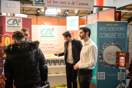 career path: STRASBOURG, FRANCE - FEB 4, 2016: Children and teens of all ages attending annual Education Fair to choose career path and receive vocational counseling - Credit Agricole stand
