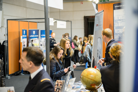 career path: STRASBOURG, FRANCE - FEB 4, 2016: Children and teens of all ages attending annual Education Fair to choose career path and receive vocational counseling - French Army recruiting