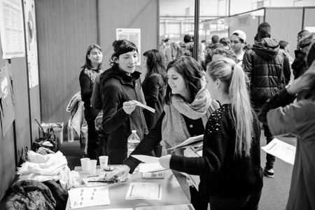 STRASBOURG, FRANCE - FEB 4, 2016: Children and teens of all ages attending annual Education Fair to choose career path and receive vocational counseling - young girls getting a flyer Editorial