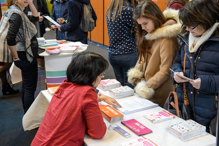 vocational: STRASBOURG, FRANCE - FEB 4, 2016: Children and teens of all ages attending annual Education Fair to choose career path and receive vocational counseling - mentor giving advice