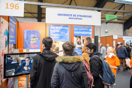 vocational: STRASBOURG, FRANCE - FEB 4, 2016: Children and teens of all ages attending annual Education Fair to choose career path and receive vocational counseling - Journalism stand