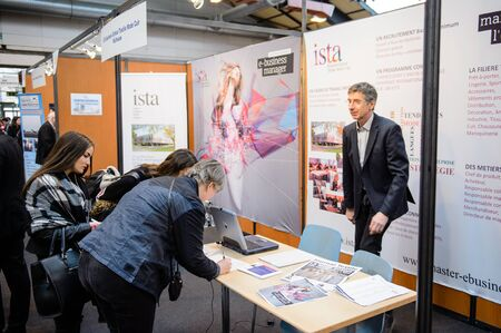 STRASBOURG, FRANCE - FEB 4, 2016: Children and teens of all ages attending annual Education Fair to choose career path and receive vocational counseling - ISTA textile school stand