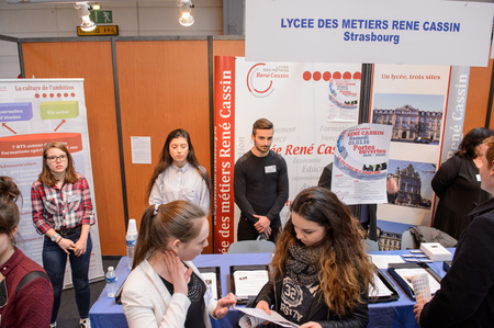 career fair: STRASBOURG, FRANCE - FEB 4, 2016: Children and teens of all ages attending annual Education Fair to choose career path and receive vocational counseling - youth group choosing at stand Editorial