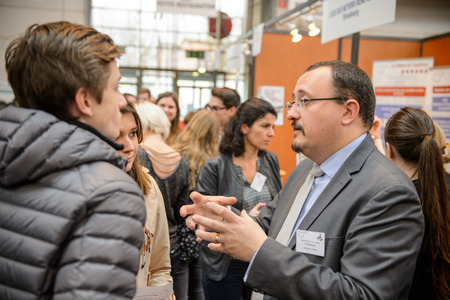 profesor: Estrasburgo, Francia - Feb 4, 2016: Los niños y adolescentes de todas las edades que asisten a la Feria anual de Educación para elegir carrera y recibir asesoramiento profesional - Profesor explicando
