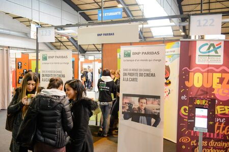 paribas: STRASBOURG, FRANCE - FEB 4, 2016: Children and teens of all ages attending annual Education Fair to choose career path and receive vocational counseling - BNP Paribas bank stand
