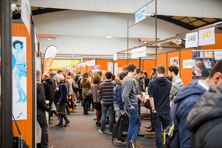 college: STRASBOURG, FRANCE - FEB 4, 2016: Children and teens of all ages attending annual Education Fair to choose career path and receive vocational counseling - rows of college stands Editorial