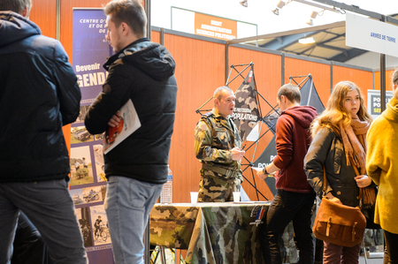 vocational: STRASBOURG, FRANCE - FEB 4, 2016: Children and teens of all ages attending annual Education Fair to choose career path and receive vocational counseling - French Army stand