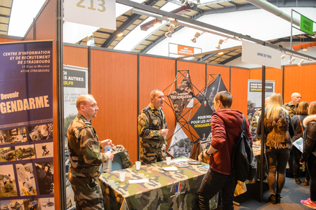 career fair: STRASBOURG, FRANCE - FEB 4, 2016: Children and teens of all ages attending annual Education Fair to choose career path and receive vocational counseling - French Army stand