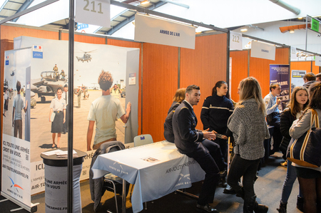career fair: STRASBOURG, FRANCE - FEB 4, 2016: Children and teens of all ages attending annual Education Fair to choose career path and receive vocational counseling - French Air Force stand