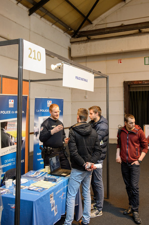 career path: STRASBOURG, FRANCE - FEB 4, 2016: Children and teens of all ages attending annual Education Fair to choose career path and receive vocational counseling - French police recruiting Editorial