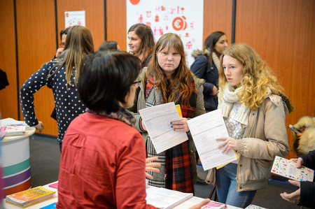STRASBOURG, FRANCE - FEB 4, 2016: Children and teens of all ages attending annual Education Fair to choose career path and receive vocational counseling - friends receiving advice Editorial