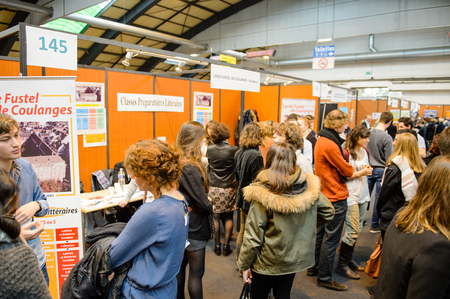 STRASBOURG, FRANCE - FEB 4, 2016: Children and teens of all ages attending annual Education Fair to choose career path and receive vocational counseling - Fustel de Coulanges lyceum stand