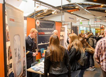 career fair: STRASBOURG, FRANCE - FEB 4, 2016: Children and teens of all ages attending annual Education Fair to choose career path and receive vocational counseling - French Marine Force