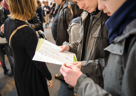 education: STRASBOURG, FRANCE - FEB 4, 2016: Children and teens of all ages attending annual Education Fair to choose career path and receive vocational counseling - bous reading flyer