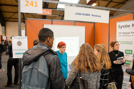 career fair: STRASBOURG, FRANCE - FEB 4, 2016: Children and teens of all ages attending annual Education Fair to choose career path and receive vocational counseling - Lycee Kleber Stand