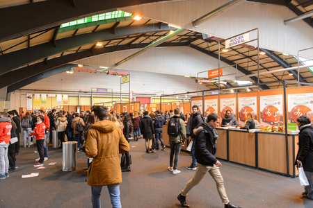 STRASBOURG, FRANCE - FEB 4, 2016: Children and teens of all ages attending annual Education Fair to choose career path and receive vocational counseling - people walking between stands