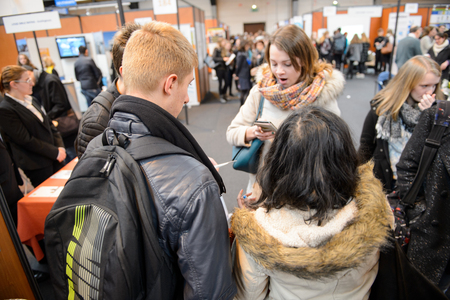 STRASBOURG, FRANCE - FEB 4, 2016: Children and teens of all ages attending annual Education Fair to choose career path and receive vocational counseling - group deciding where to go