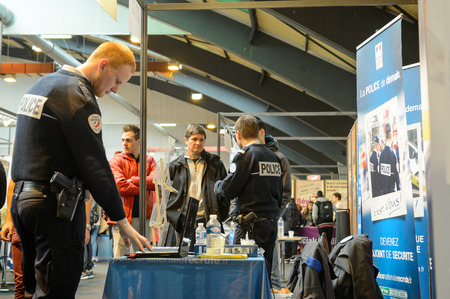 career path: STRASBOURG, FRANCE - FEB 4, 2016: Children and teens of all ages attending annual Education Fair to choose career path and receive vocational counseling - French Police stand Editorial