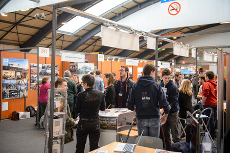 STRASBOURG, FRANCE - FEB 4, 2016: Children and teens of all ages attending annual Education Fair to choose career path and receive vocational counseling - busy college stand Éditoriale