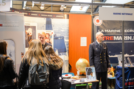 career path: STRASBOURG, FRANCE - FEB 4, 2016: Children and teens of all ages attending annual Education Fair to choose career path and receive vocational counseling - French Marine recruiting