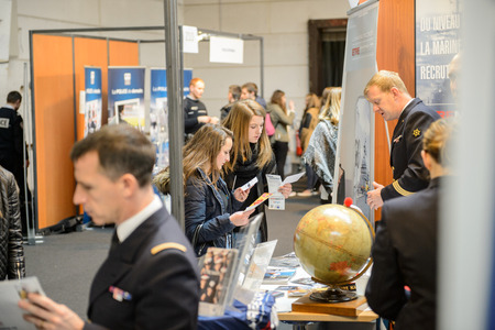 career fair: STRASBOURG, FRANCE - FEB 4, 2016: Children and teens of all ages attending annual Education Fair to choose career path and receive vocational counseling - French Army recruiting