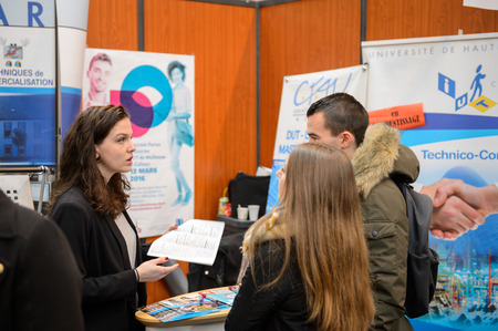 career fair: STRASBOURG, FRANCE - FEB 4, 2016: Children and teens of all ages attending annual Education Fair to choose career path and receive vocational counseling - teens receiveing advices at stand