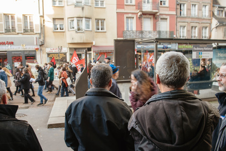 extent: STRASBOURG, FRANCE - FEB 6, 2016: Turkish ethnicity men looking at protesters marching during a demonstration against governments plan to extent the state of emergency and for opened borders -