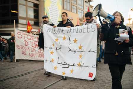 extent: STRASBOURG, FRANCE - FEB 6, 2016: Protesters marching during a demonstration against governments plan to extent the state of emergency and for opened borders - holding welcome refugees banners Editorial