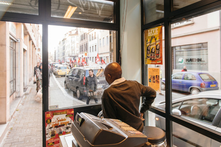 french ethnicity: STRASBOURG, FRANCE - FEB 6, 2016: Black ethnicity shop owner looking from the store to the protesters marching during a demonstration against governments plan to extent the state of emergency and for opened borders