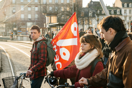 precarious: STRASBOURG, FRANCE - FEB 6, 2016: Communist flags in hands of protesters marching during a demonstration against governments plan to extent the state of emergency and for opened borders